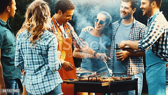 Closeup side view of group of mid 20's people having backyard barbecue party. There are three guys and four girls gathered around heavily smoking grill and sipping cold beer. One of the guys is being today's chef. Toned image, mild contrast, back lit.