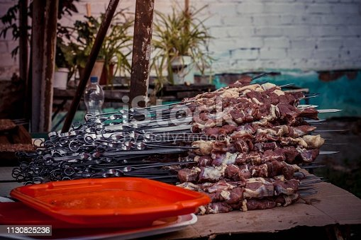 skewers with meat are on the street on the table near the cafe