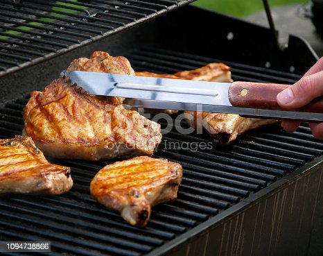 Barbecuing pork chops on the grill in the summer.