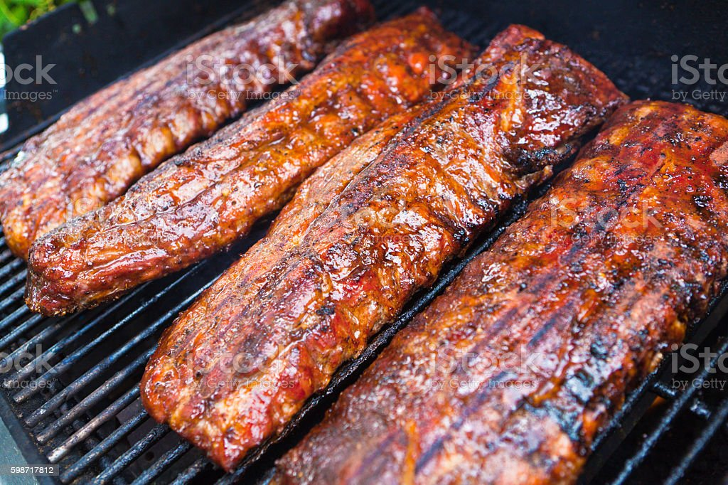 Barbecue Pork Ribs Cooking on the Grill in Pit stock photo