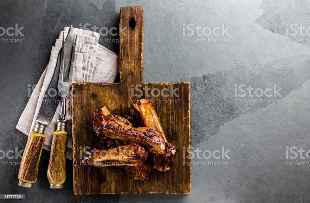 Barbecue pork ribs on wooden cutting board and vintage cutlery set on slate background. Copy space stock photo