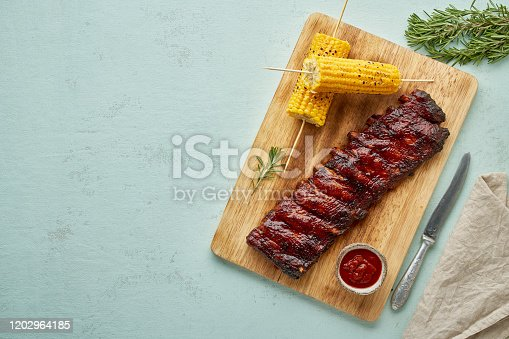 Barbecue pork ribs. Slow cooking recipe. Whole pickled roasted pork meat with red sauce and corn on cutting board, copy space, top view. Turquoise background
