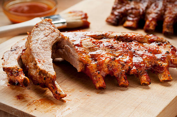 Barbecue Ribs Barbecue ribs with sauce on a cutting board. pork stock pictures, royalty-free photos & images