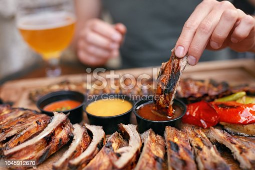 Barbecue Ribs With Sauсes Closeup. Man's Hand With Spareribs. High Resolution