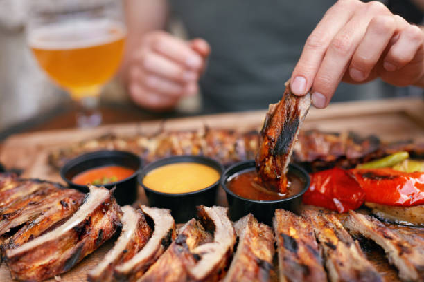 Barbecue Ribs With Sauсes Closeup Barbecue Ribs With Sauсes Closeup. Man's Hand With Spareribs. High Resolution sauce stock pictures, royalty-free photos & images