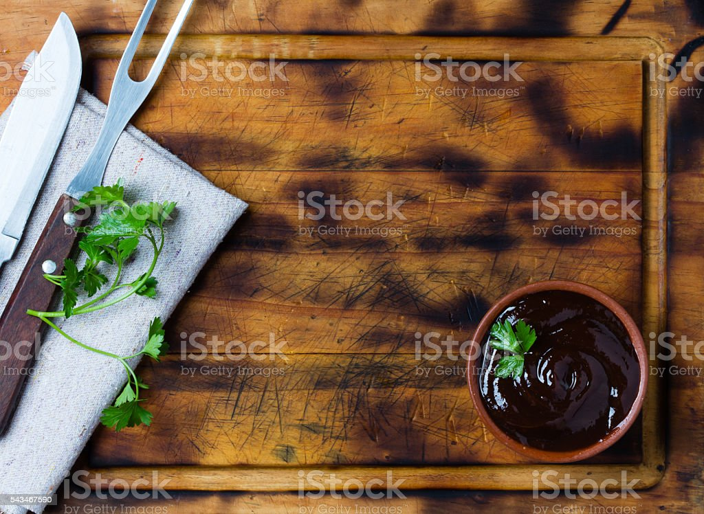 Barbecue sauce in clay bowl, meat fork, knife, cutting board. stock photo