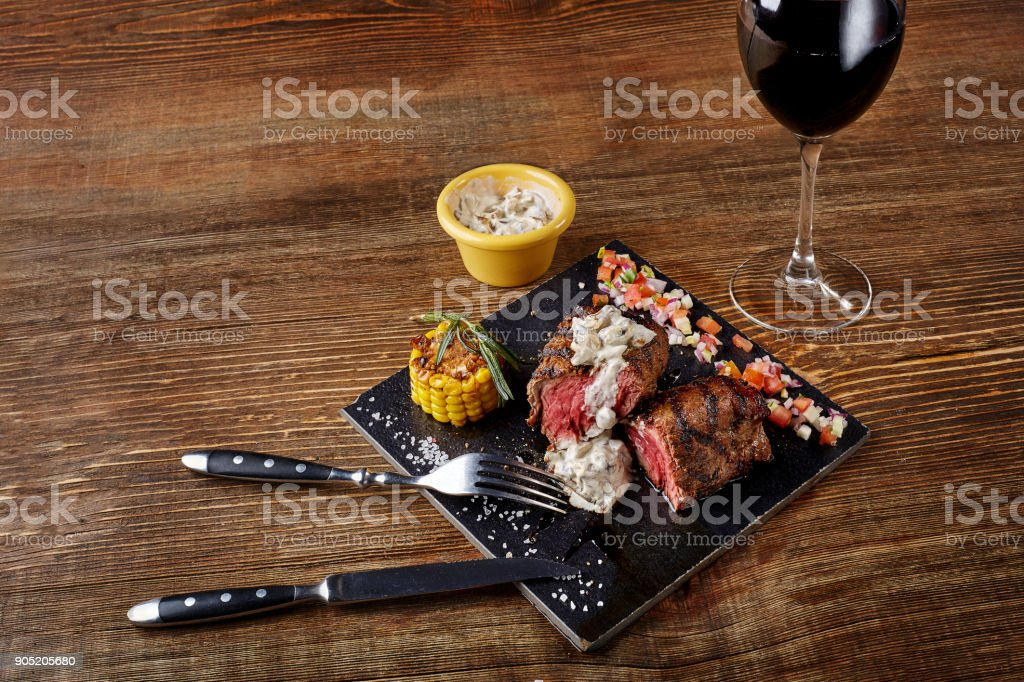 Barbecue steak with a glass of red wine as close-up on black board on wooden background stock photo