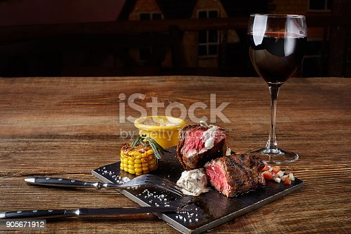 istock Barbecue steak with a glass of red wine as close-up on black board on wooden background 905671912