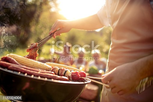 Men are cooking for family having barbecue party in garden on summer. Close up of hand cooking meat on barbecue.