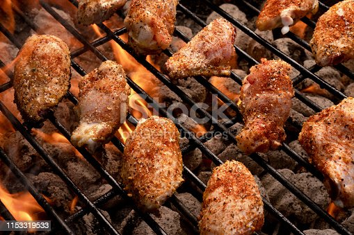 Hot and spicy grilled buffalo chicken wings cooking on a grill with flames