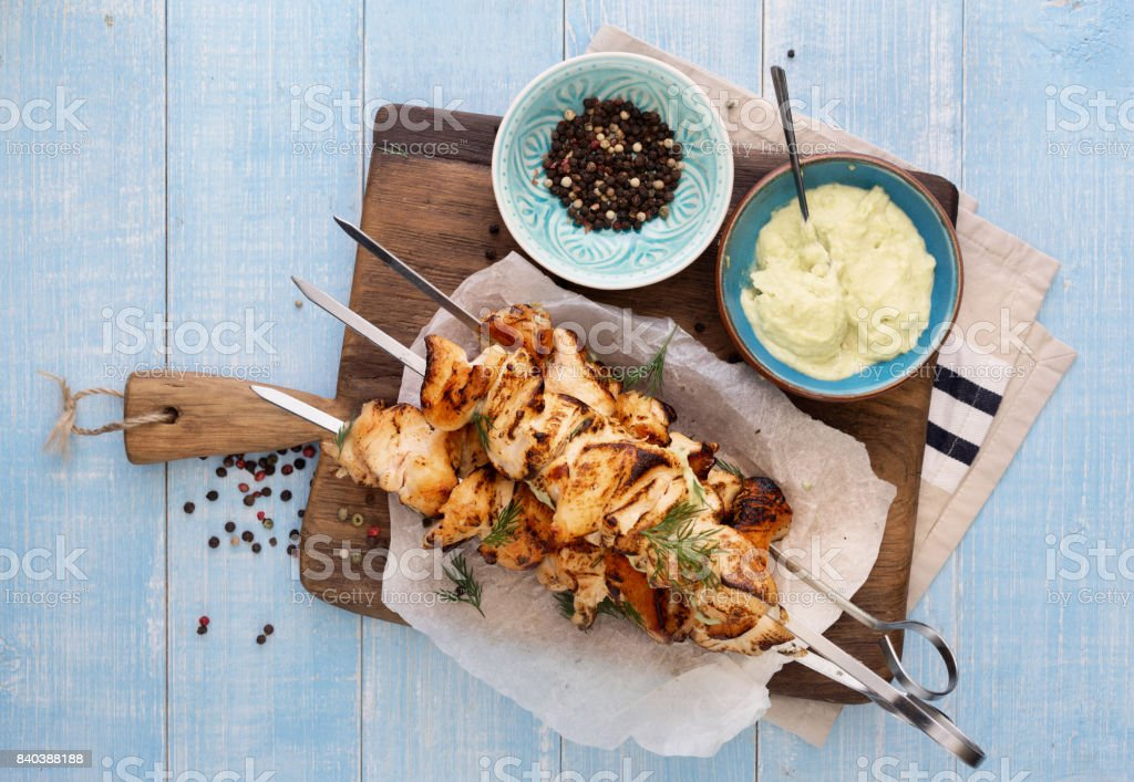 Barbecued chicken breast skewers with avocado sauce on blue wooden table stock photo