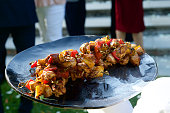 Barbecued Chicken kebabs on a service dish balanced being held by a waiter Cape Town South Africa