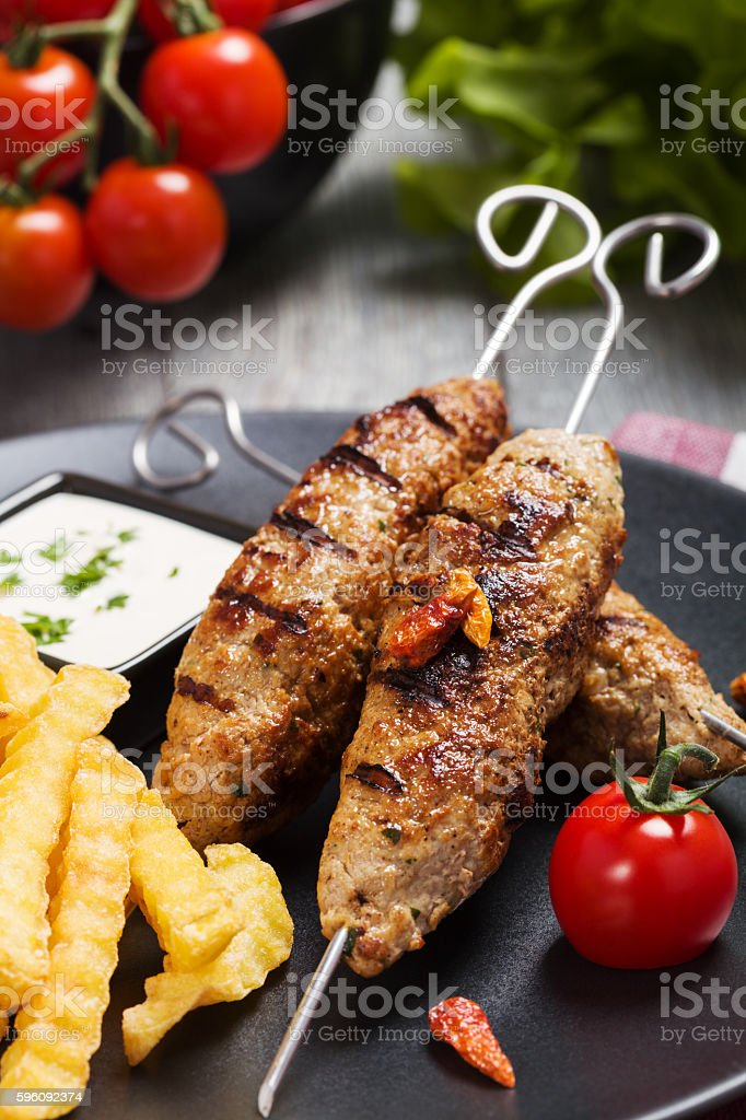 Barbecued kofta - kebeb with fries and vegetables royalty-free stock photo