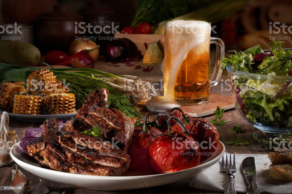 Barbecued meat, tomatoes, corn on a wooden table with greens, salad, duck and garlic. stock photo