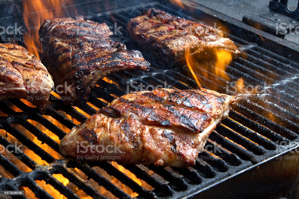 Barbecued Pork Baby Back Ribs on Fiery Charcoal Grill stock photo