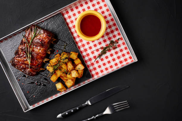 Barbecued ribs with baked potato and hot chili sauce Barbecued ribs with baked potato and hot chili sauce on an iron tray. Black background human rib cage stock pictures, royalty-free photos & images