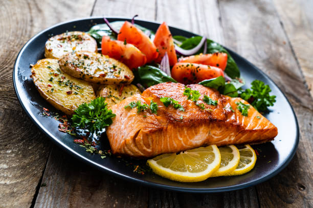 Barbecued salmon, fried potatoes and vegetables on wooden background stock photo