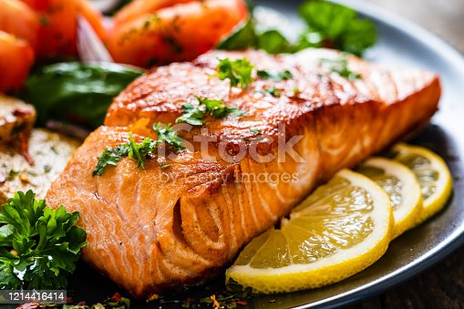 istock Barbecued salmon, fried potatoes and vegetables on wooden background 1214416414