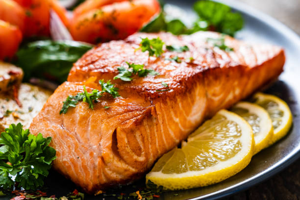 Barbecued salmon, fried potatoes and vegetables on wooden background Barbecued salmon, fried potatoes and vegetables on wooden background cooked stock pictures, royalty-free photos & images