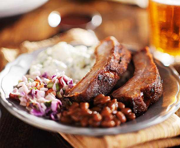 barbecued spare rib meal with beer and fixings stock photo