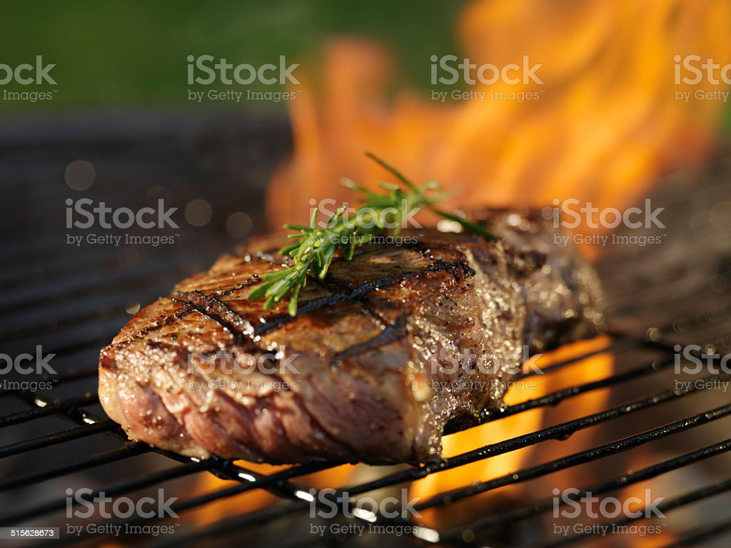 barbecueing steak stock photo