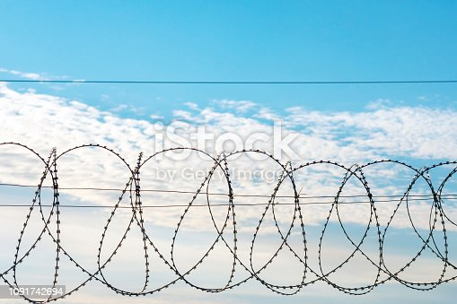 486568999istockphoto Barbed wire against a blue sky. 1091742694