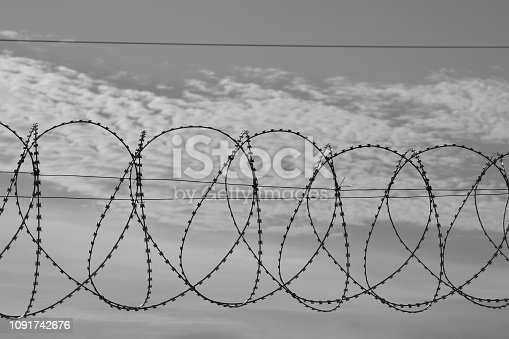 486568999istockphoto Barbed wire against a sky with feathery clouds. 1091742676