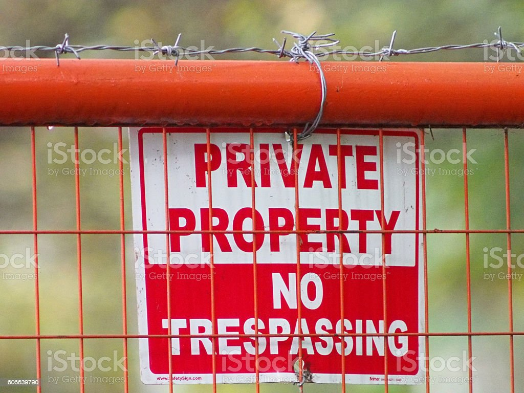 Barbed Wire and No Trespassing Sign on Fence stock photo