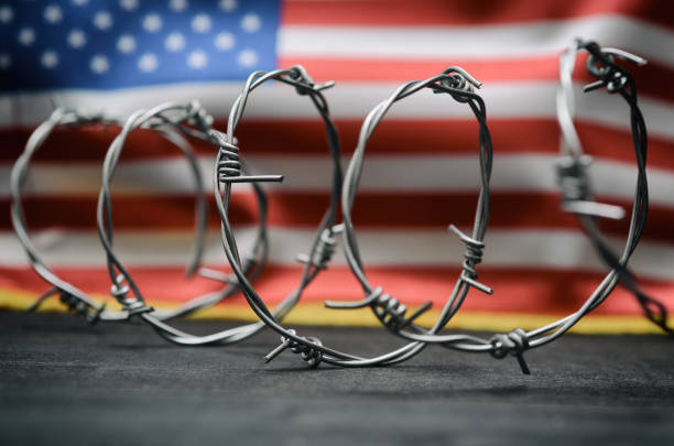 Barbed wire and United States of America flag , immigration stock photo Barbed wire and United States of America flag , immigration  concept. deportation stock pictures, royalty-free photos & images