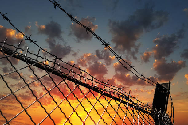 Barbed wire fence against a dramatic sky at sunset. The concept of restriction of freedom of movement. Barbed wire fence against a dramatic sky at sunset. The concept of restriction of freedom of movement, human rights violations. genocide stock pictures, royalty-free photos & images