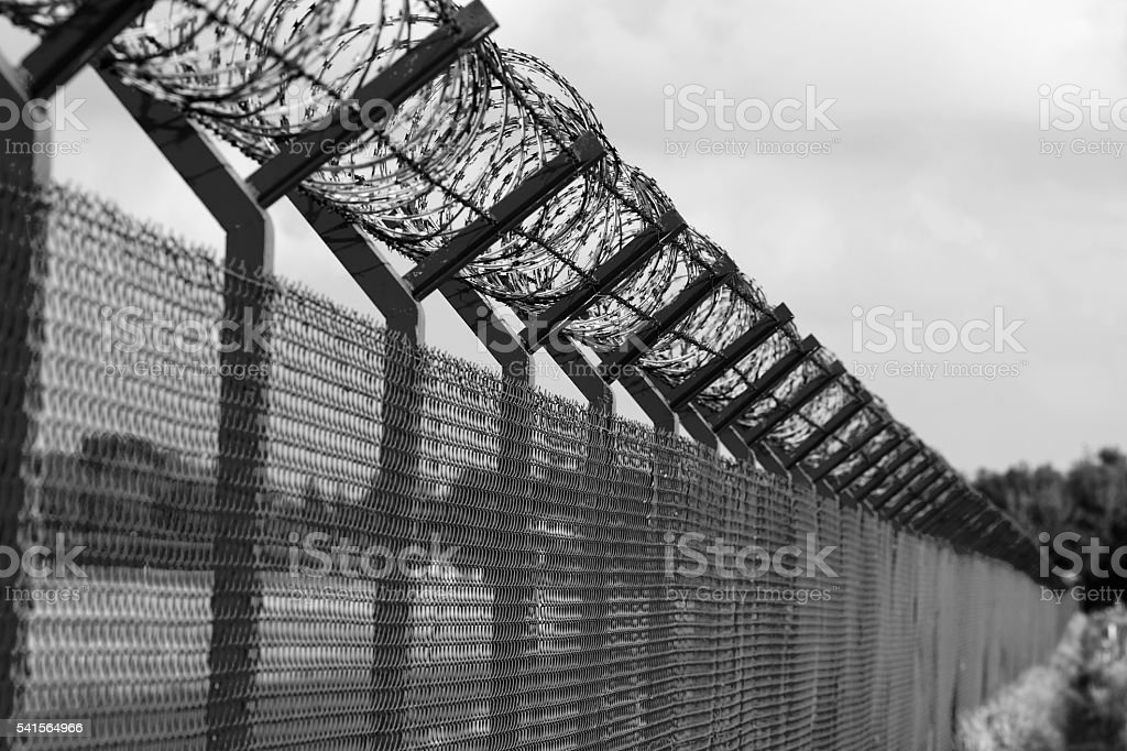 Barbed wire fence of a restricted area, black and white stock photo
