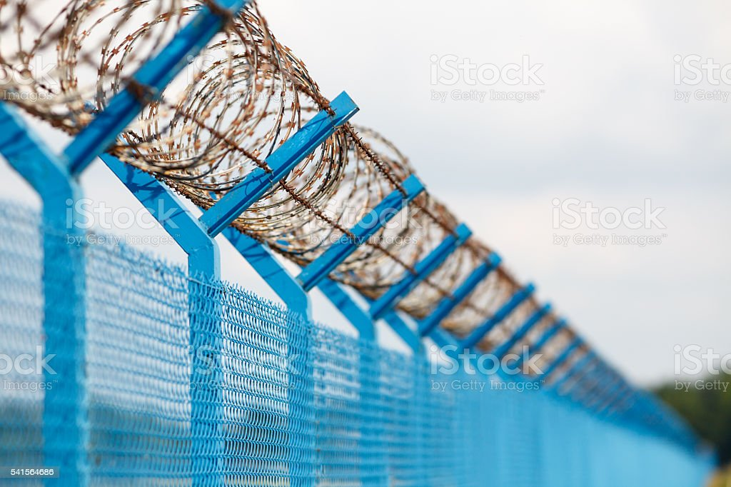 Barbed wire fence of a restricted area under blue sky stock photo