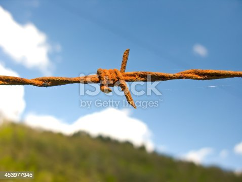 91708255 istock photo Barbed wire fence, over a blue sky. Detail close up. 453977945
