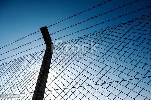 Barbed wire fence, low angle view
