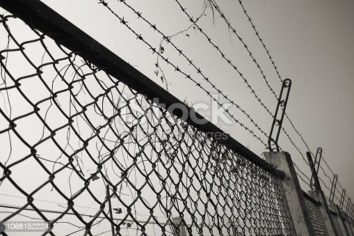 istock Barbed Wire Fence Prison Fence in Black and White 1068152224