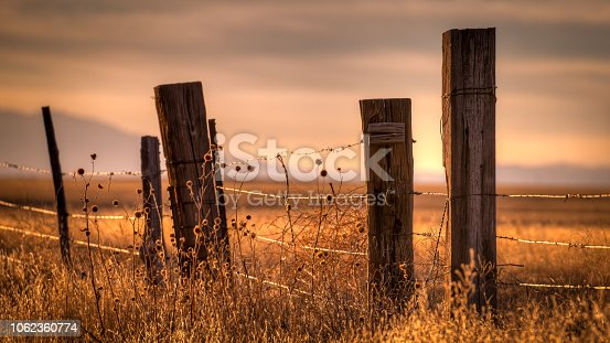 istock Barbed Wire Fence Protecting Farmland 1062360774