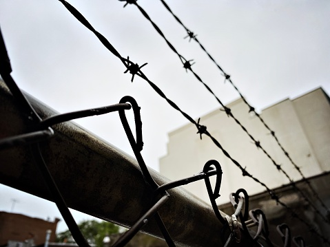 Barbed Wire Fence Top with Foreboding Building