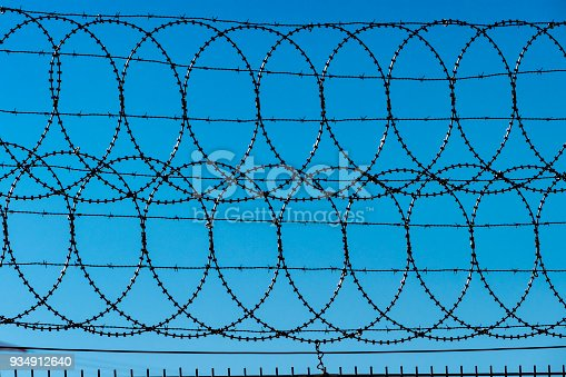 Barbed wire fence with blue sky in the background