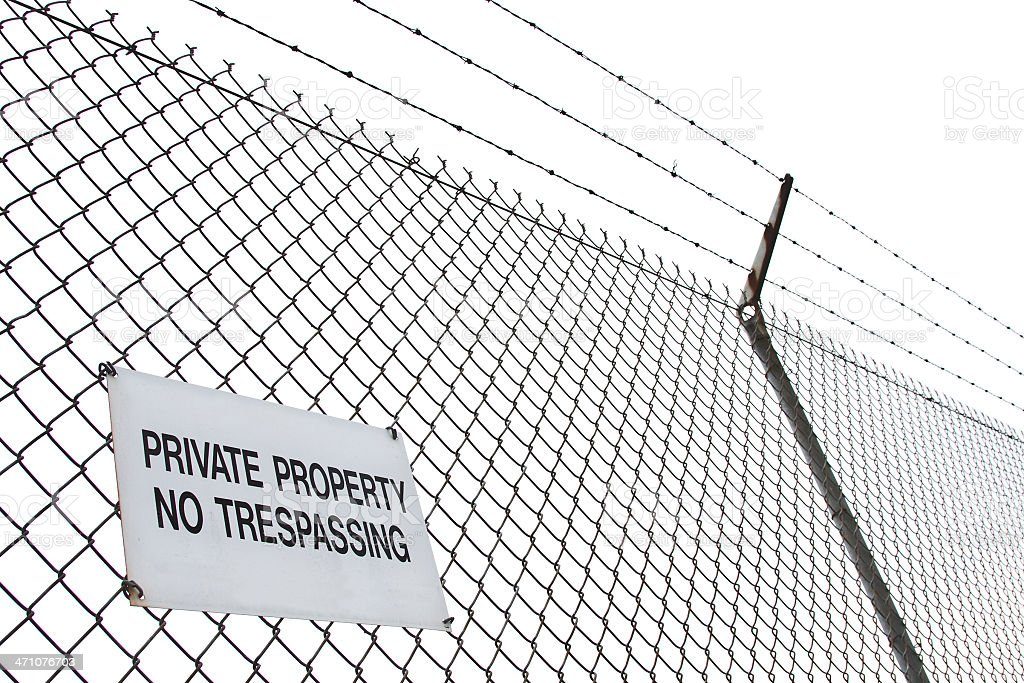 barbed wire fence with no trespassing sign stock photo