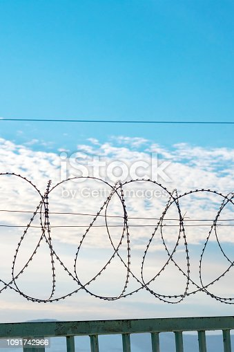 486568999istockphoto Barbed wire on a metal fence. Behind the fence is a blue sky with feathery clouds. 1091742966