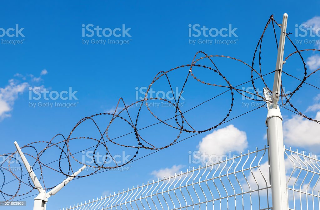 Barbed wire on blue sky background stock photo