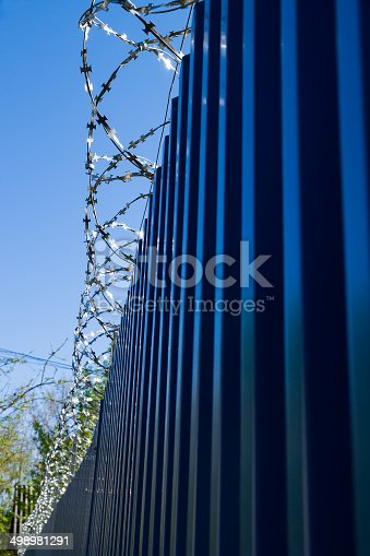 486568999istockphoto Barbed wire on fence 498981291