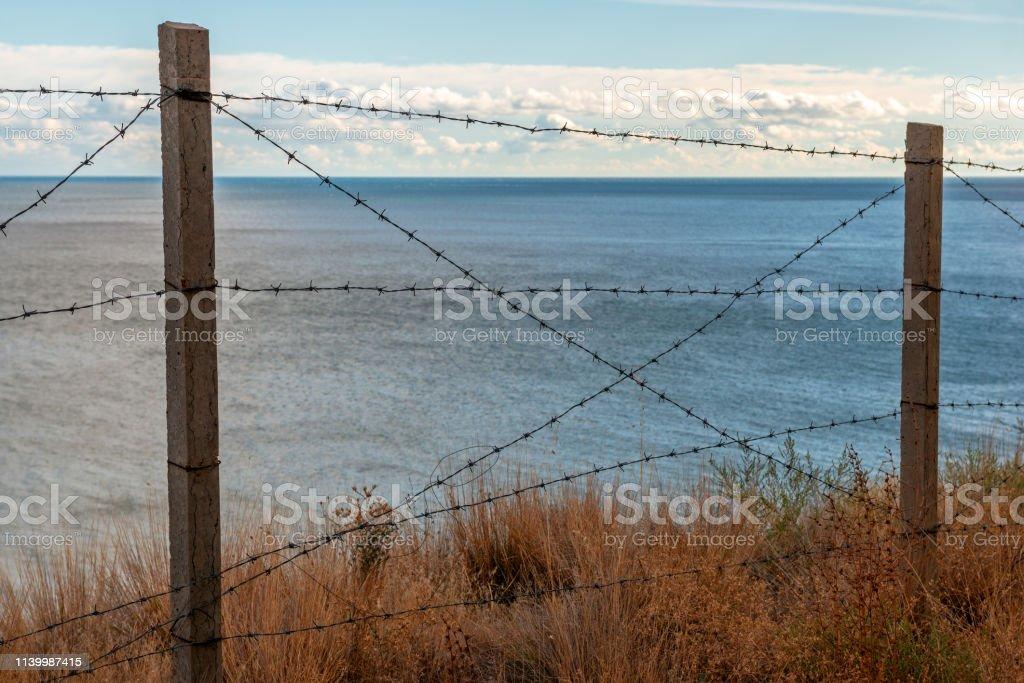 Barbed wire on sea coast stock photo