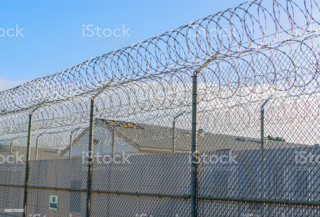 Barbed wire prison fence stock photo