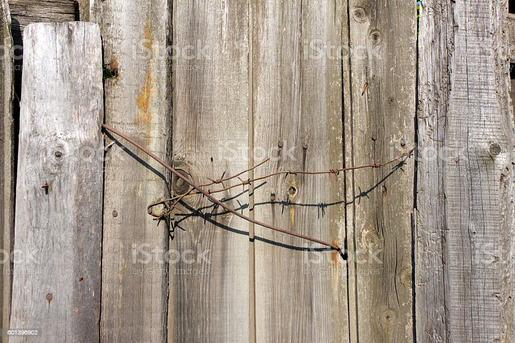 Barbed wire sticking out of the wooden fence. stock photo