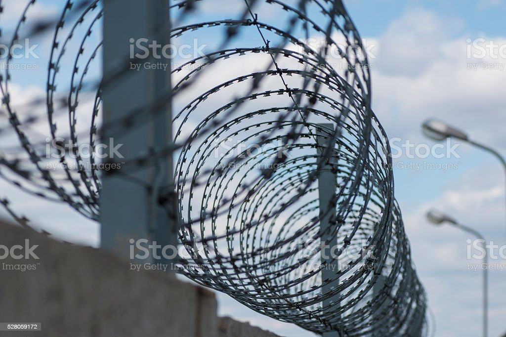 Barbed wire stretched along the brick  walls stock photo