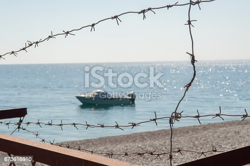 istock Barbed wire with dragonfly and sea 673616910