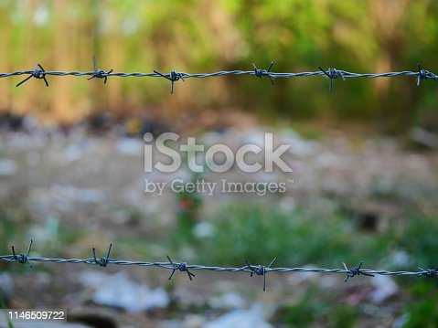 91708255 istock photo Barbed wire with green background 1146509722