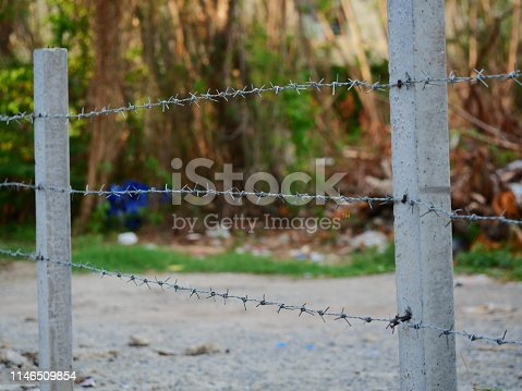 91708255 istock photo Barbed wire with green background 1146509854