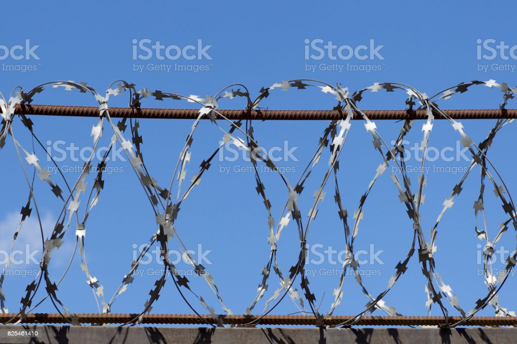 Barbed Wire Wound To The Top Of A Fence stock photo | iStock